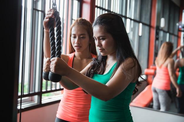 Chiuda in su della giovane donna che esercita il pushdown del tricipite con l'istruttore