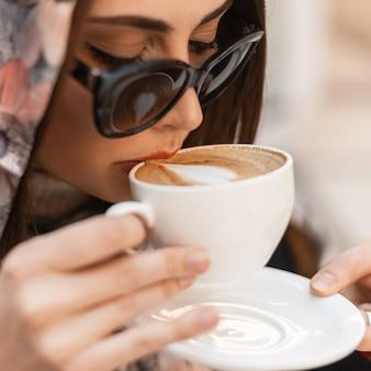 Giovane donna del primo piano in occhiali da sole alla moda in sciarpa elegante sulla testa con caffè caldo aromatico della tazza in caffè. la ragazza attraente beve il latte all'interno. mattinata per gli amanti della caffeina. colazione. buon giorno