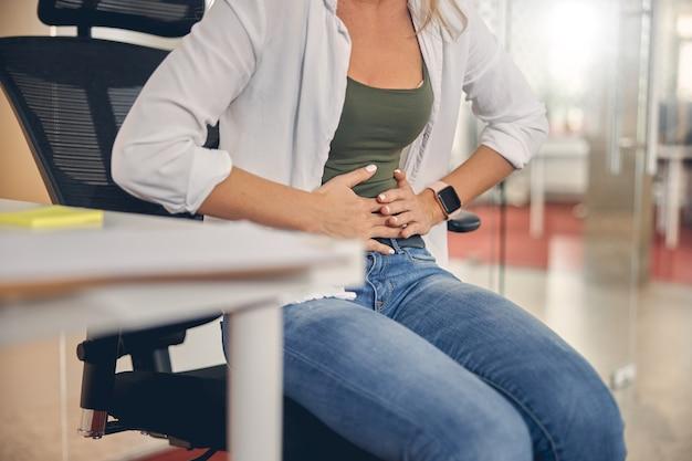 Primo piano di una giovane donna che sente dolore allo stomaco mentre è seduta su una sedia al lavoro