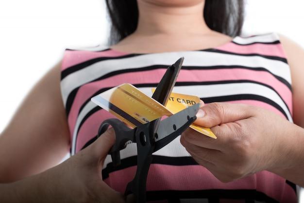 Chiuda sulla mano della giovane donna che taglia una carta di credito con le forbici per smettere di spendere per lo shopping