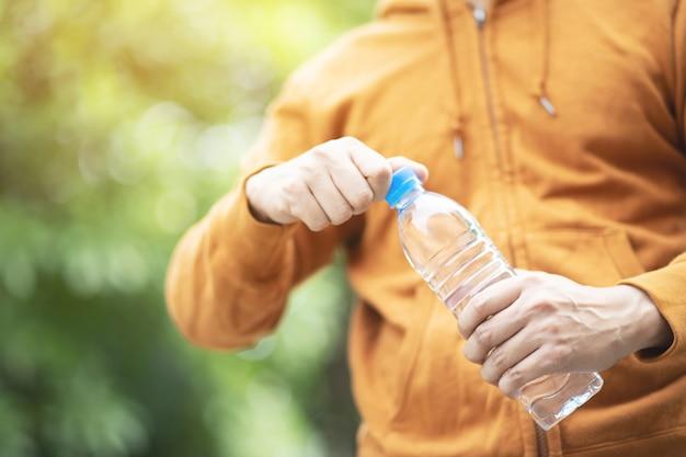 Chiuda sulla mano della giovane donna che tiene la bottiglia di acqua potabile fresca da una plastica nel parco.