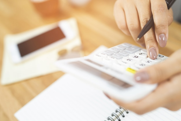 Primo piano mano giovane donna sta scrivendo in un taccuino e utilizzando il conteggio calcolatrice prendere appunti contabilità a fare finanza in ufficio a casa.