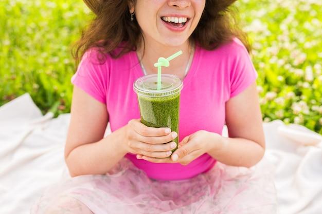 Primo piano di una giovane donna che si diverte nel parco e beve frullati verdi a un picnic