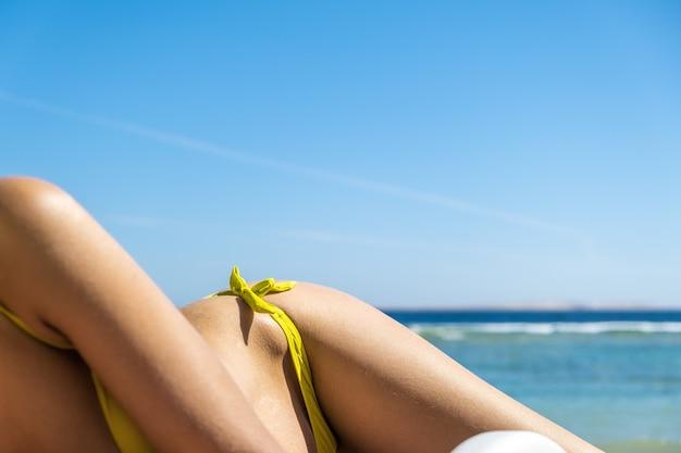 Primo piano di giovane donna anca e spalla posa sulla sedia a sdraio in riva al mare a prendere il sole.
