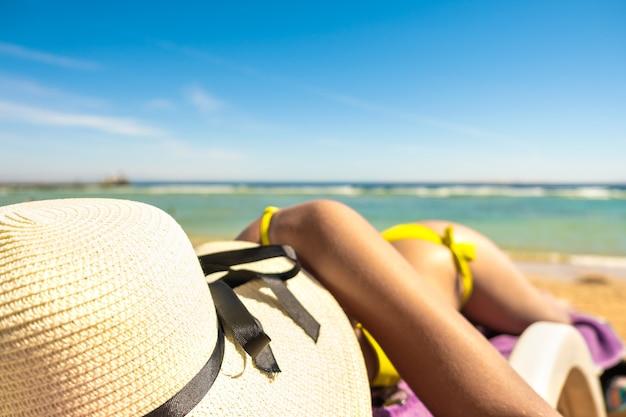 Chiuda in su dell'anca e della spalla della giovane donna che pone sulla sedia di spiaggia al puntello di mare che prende il sole.