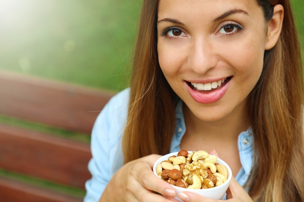 Chiuda in su della giovane donna che tiene una ciotola di noci miste nel parco.