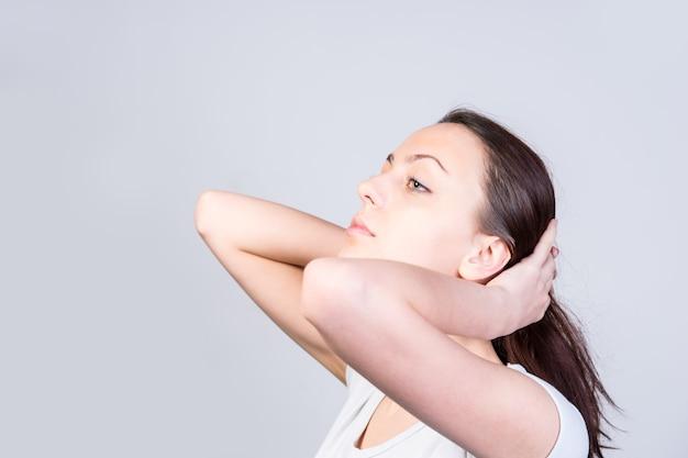 Close up giovane donna che tiene i suoi lunghi capelli indietro con il mento mentre guarda a sinistra del telaio