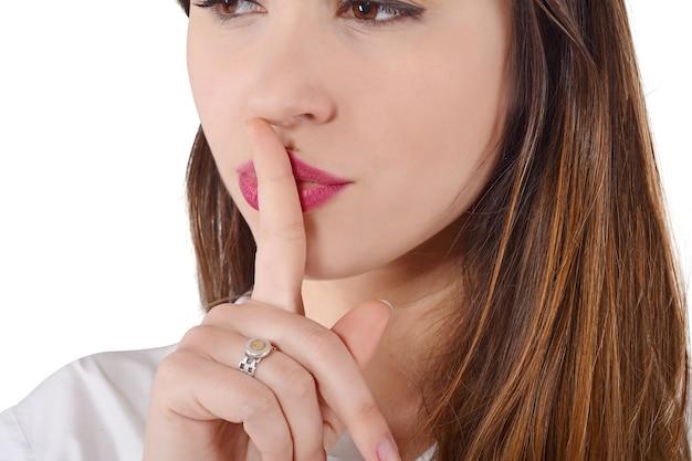 Chiuda in su della giovane donna che fa gesto di silenzio.