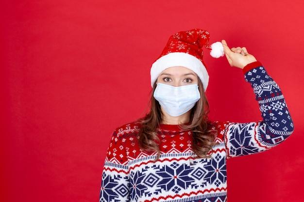 Chiudere una giovane donna in una maschera medica, cappello di babbo natale che tiene un pompon