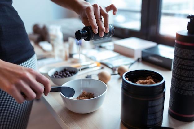 Primo piano di una giovane donna che prepara la crema al cioccolato con ingredienti naturali per il trattamento del corpo. concetto di cura del corpo.