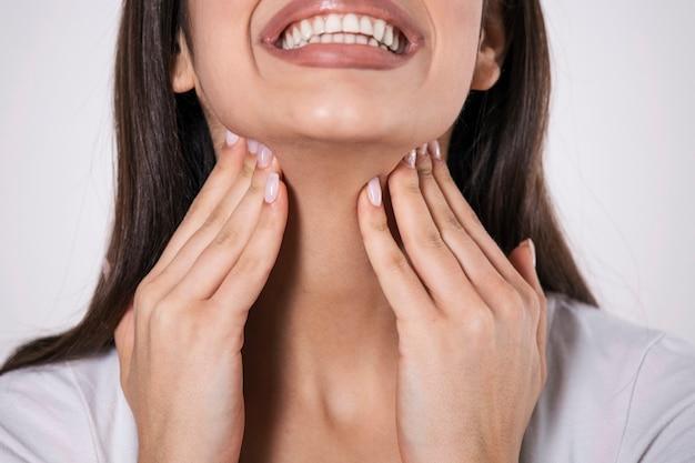 Primo piano di giovane donna strofinando le tonsille infiammate, problema di tonsillite, ritagliata.