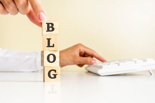 Chiuda sulla mano della giovane donna nel cubo del blocco di legno della camicia bianca per la formulazione del blog sul pavimento del tavolo bianco, tastiera bianca sullo sfondo. concetti finanziari, di marketing e di business