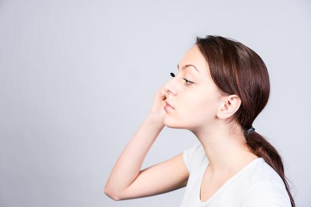 Chiuda sulla giovane donna in vista laterale che applica il trucco del mascara mentre guarda a sinistra del telaio.