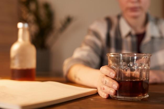 Primo piano di giovane donna seduta al tavolo e bere cocktail alcolici a casa