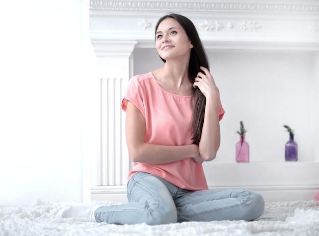 Close up. giovane donna seduta sul tappeto bianco nel soggiorno.