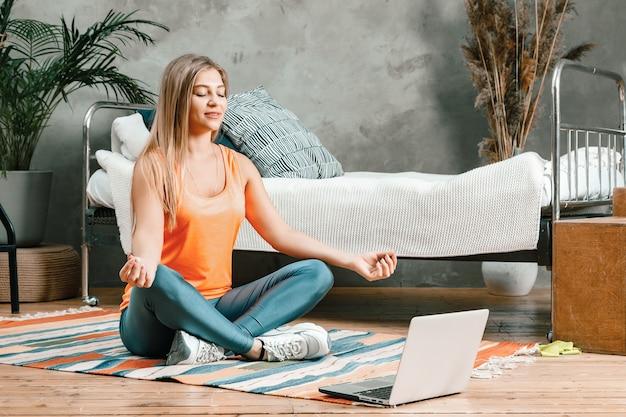 Primo piano di una giovane donna in uniforme sportiva medita nella posizione del loto, allungandosi sul pavimento a casa