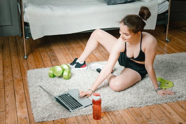 Primo piano di una giovane donna in uniforme sportiva è appoggiato sul pavimento a casa, guarda un film e studia da un laptop, un social network