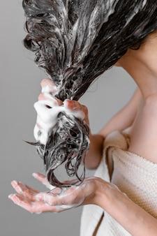 Capelli di lavaggio della giovane donna del primo piano