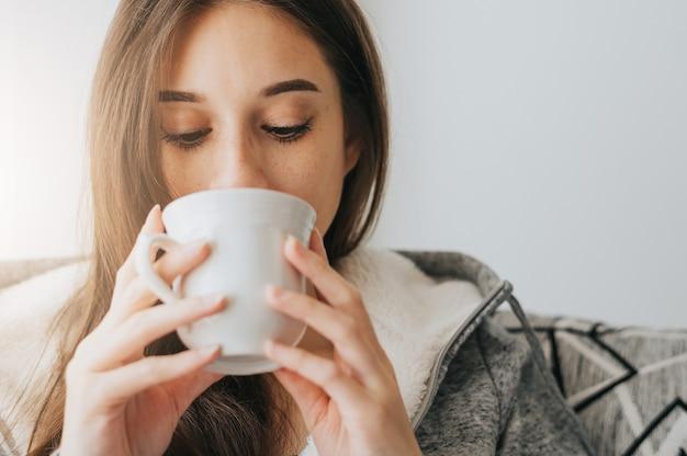 Primo piano di giovane donna che indossa un maglione sorseggiando caffè o tè dalla tazza bianca al mattino