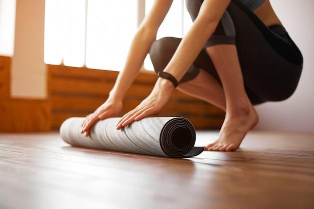 Primo piano di giovane donna con la stuoia di esercizio che prepara per l'allenamento sportivo