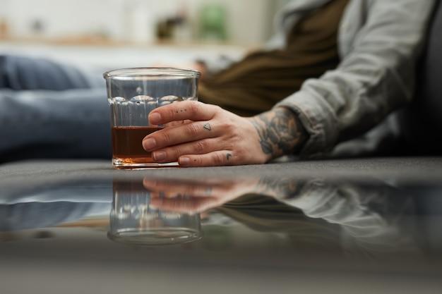 Primo piano di giovane donna con un bicchiere di whisky seduto sul pavimento e bere a casa