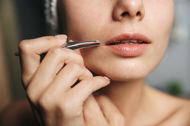 In prossimità di una giovane donna con un asciugamano sulla testa rimuovendo i capelli sopra il labbro con una pinzetta davanti allo specchio in bagno