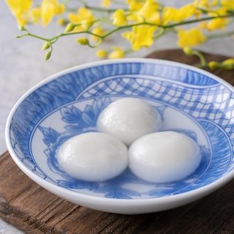Close up yuanxiao tangyuan (palle di gnocchi di riso glutinoso) in una ciotola sul tavolo grigio con fiori, cibo per il festival cinese delle lanterne yuanxiao.