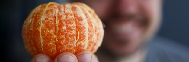 Primo piano della frutta sana squisita del mandarino. colpo a macroistruzione dell'uomo che tiene mandarino arancione luminoso sulla macchina fotografica. copia spazio sul lato destro. concetto di snack deliziosi esotici