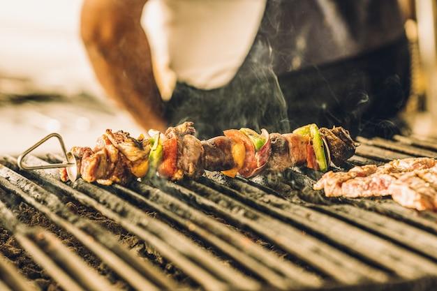 Primo piano di squisiti spiedini di carne con verdure che cucinano alla griglia.