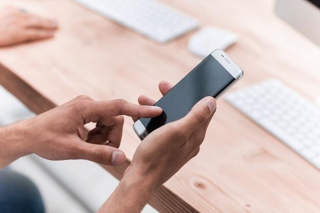 Primo piano uomo d'affari utilizza il suo smartphone sul posto di lavoro. persone e tecnologia