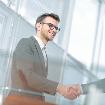 Close upmodern giovane stringendo la mano con il manager