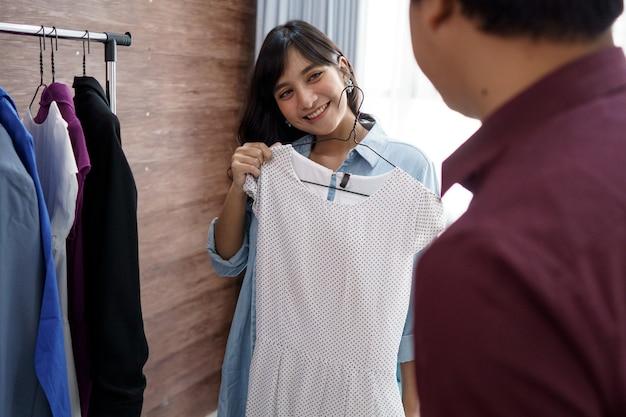 Primo piano di una coppia allegra che sceglie e compra vestiti. al negozio di vestiti