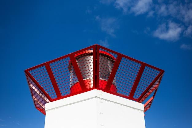 Vista ravvicinata del faro sul cielo blu.