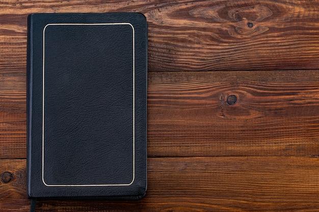 Bibbia chiusa su fondo di legno, spazio della copia. vista dall'alto.