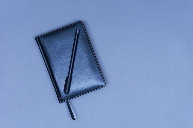 Un taccuino chiuso in pelle nera giace sul tavolo con una penna per appunti.