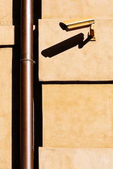 Telecamera a circuito chiuso (cctv) su una parete di un edificio giallo. concetto di sicurezza.
