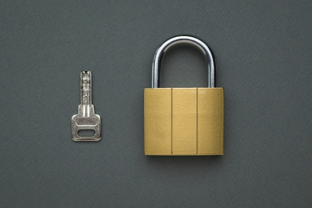Serratura classica chiusa e chiave su un tavolo grigio. il concetto di protezione e sicurezza. lay piatto.