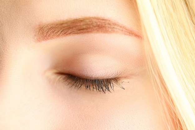 Occhio chiuso di bella donna bionda in primo piano del sole del mattino