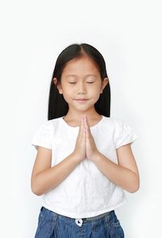 Piccola preghiera asiatica della ragazza del bambino degli occhi chiusi isolata