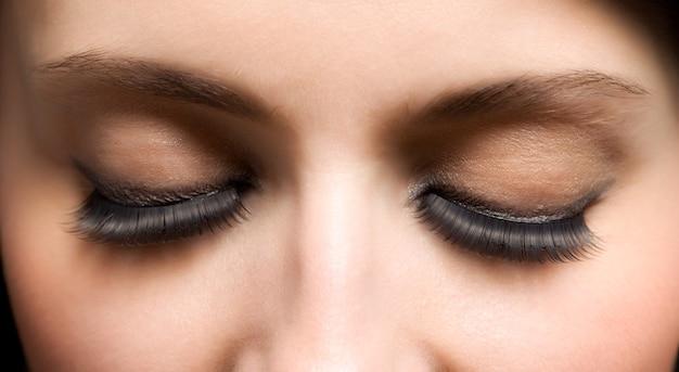 Occhi chiusi del fronte della giovane donna con ciglia estese