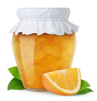 Barattolo di vetro chiuso con coperchio di carta con marmellata di arance e un pezzo di frutta fresca di arancia isolato su bianco