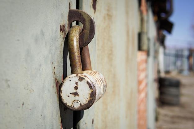 Porta del garage chiusa in ferro con vecchio lucchetto