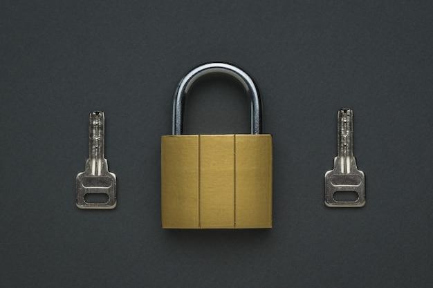 Una serratura chiusa con due chiavi. il concetto di protezione e sicurezza. lay piatto.