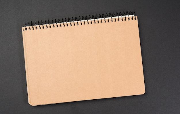 Blocco note chiuso con fogli marroni su sfondo nero, da vicino