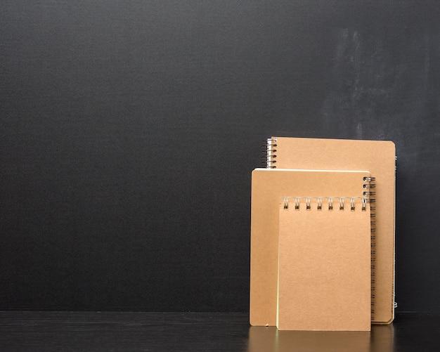 Blocco note chiuso con fogli marroni su sfondo nero, copia dello spazio