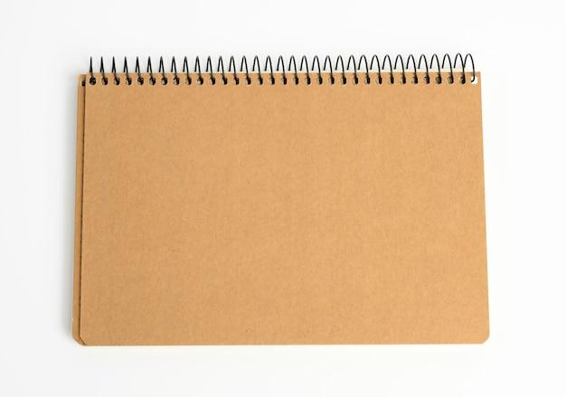 Blocco note chiuso con fogli marroni su sfondo bianco, da vicino