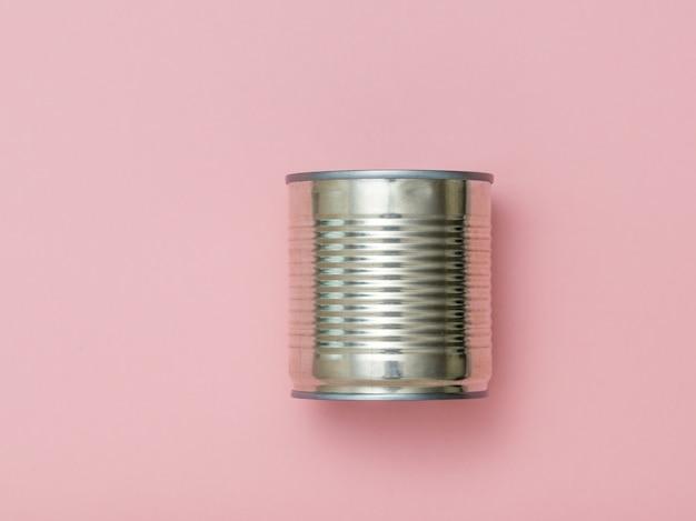 Barattolo di latta chiuso e forchetta su uno sfondo rosa. contenitore universale per conserve.