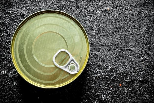 Barattolo di latta chiuso con cibo in scatola sul tavolo rustico nero.