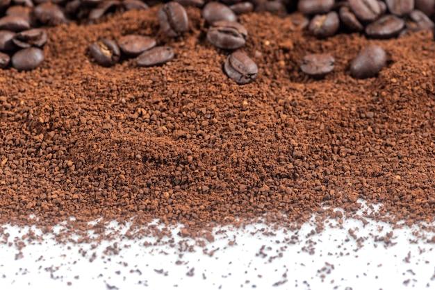 Caffè macinato chiuso in polvere e chicchi arrosto sfocati