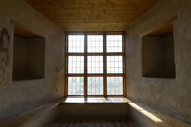 Finestra in legno chiusa con due fori quadrati uno di fronte all'altro cementati sul pavimento e sul soffitto a bordo con la luce del sole che entra